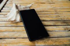 Τα άτομα με ειδικές ανάγκες τηλεφωνούν, όμορφο θαλασσινό κοχύλι σε έναν πίνακα μπαμπού σε έναν καφέ Στοκ εικόνα με δικαίωμα ελεύθερης χρήσης