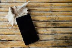 Τα άτομα με ειδικές ανάγκες τηλεφωνούν, όμορφο θαλασσινό κοχύλι σε έναν πίνακα μπαμπού σε έναν καφέ Στοκ Φωτογραφίες