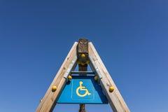 Τα άτομα με ειδικές ανάγκες υπογράφουν και simbol στον ξύλινο πόλο ταλάντευσης, παιδική χαρά με το γ Στοκ Εικόνα