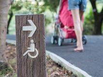 Τα άτομα με ειδικές ανάγκες υπογράφουν στο πάρκο με το μουτζουρωμένο περιπατητή ώθησης μητέρων κατά μήκος της διάβασης Στοκ Φωτογραφίες