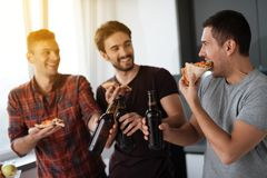 Τα άτομα πίνουν την μπύρα και τρώνε την πίτσα στην κουζίνα Μιλούν και έχουν έναν μεγάλο χρόνο Στοκ Εικόνα