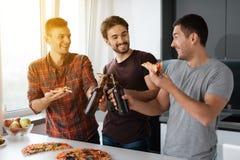 Τα άτομα πίνουν την μπύρα και τρώνε την πίτσα στην κουζίνα Μιλούν και έχουν έναν μεγάλο χρόνο Στοκ Εικόνες