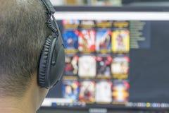 Τα άτομα φορούν τα ακουστικά στη οθόνη υπολογιστή Στοκ Φωτογραφίες
