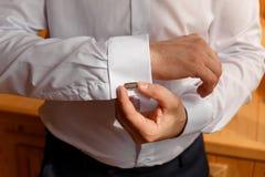 Τα άτομα φορούν τα μανικετόκουμπα σε ένα μανίκι πουκάμισων Στοκ εικόνα με δικαίωμα ελεύθερης χρήσης