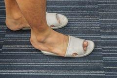 Τα άτομα φορούν το πάρα πολύ σφιχτό σανδάλι στα πόδια του στο σπίτι Στοκ Εικόνες