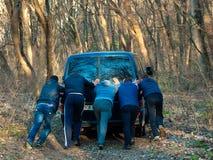 Τα άτομα ωθούν το αυτοκίνητο ÐœÑƒÐ¶Ñ ‡ иР½ Ñ ‹Ñ 'Ð ¾ л ÐºÐ°ÑŽÑ 'Ð ¼ ашиР½ у Στοκ Φωτογραφίες