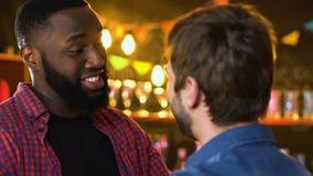Τα άτομα Multiethnic που αγκαλιάζουν στο μπαρ, αναμενόμενη για καιρό συνεδρίαση δύο παλιών φίλων, χαλαρώνουν φιλμ μικρού μήκους