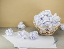 Τα άχρηστα χαρτιά στο δοχείο είναι υπερχείλιση στον πίνακα εργασίας Στοκ Εικόνες
