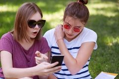 Τα έκπληκτα ελκυστικά θηλυκά εξετάζουν την οθόνη του έξυπνου τηλεφώνου, λαμβάνουν το απροσδόκητο μήνυμα από τον ξένο, σκέφτονται  Στοκ φωτογραφίες με δικαίωμα ελεύθερης χρήσης