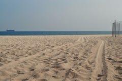 Τα ίχνη ροδών αυτοκινήτων οδηγούν κατά μήκος της άμμου σε έναν φράκτη καλωδίων σε μια κενή παραλία θάλασσας στοκ εικόνες