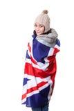 τα αγγλικά μαθαίνουν Όμορφα βιβλία εκμετάλλευσης σπουδαστών Νέα γυναίκα που στέκεται με τη βρετανική σημαία στο υπόβαθρο που ανατ Στοκ Φωτογραφία