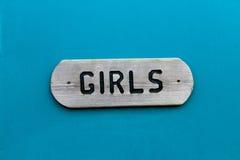 Τα αγροτικά κορίτσια υπογράφουν στην μπλε πόρτα Στοκ Φωτογραφία