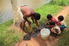 Τα αγροτικά παιδιά κάνουν την αλιεία στα τέλματα Στοκ Φωτογραφίες