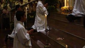 Τα αγόρια βωμών γονατίζουν στην εκκλησία κατά τη διάρκεια του μαζικού εορτασμού απόθεμα βίντεο