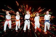 Τα αγόρια και τα κορίτσια στο κιμονό κτυπούν τα όπλα χτυπημάτων στο μαύρο υπόβαθρο με τις χρωματισμένες φλόγες Στοκ Φωτογραφίες