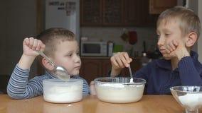 Τα αγόρια προετοιμάζουν τη ζύμη και το νεώτερο αγόρι προσθέτει το αλεύρι και τον αντίχειρα επάνω απόθεμα βίντεο