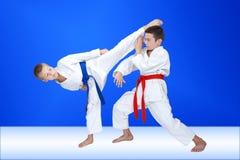 Τα αγόρια στο karategi εκπαιδεύουν ένα κυκλικούς λάκτισμα και έναν φραγμό Στοκ Φωτογραφίες