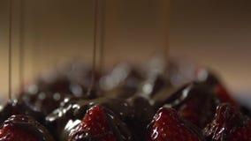 Τα αεριωθούμενα αεροπλάνα της υγρής σοκολάτας χύνονται επάνω στη φράουλα απόθεμα βίντεο