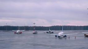 Τα αεροπλάνα στον αερολιμένα προετοιμάζονται για την πτήση με το προσγειωμένος αεροπλάνο στο υπόβαθρο απόθεμα βίντεο