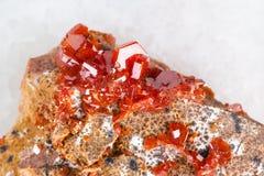 τα ακατέργαστα κρύσταλλα της πέτρας Vanadinite κλείνουν επάνω στο λευκό Στοκ Φωτογραφίες