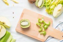 Τα ακατέργαστα πράσινα συστατικά για τα μήλα καταφερτζήδων, συνόλου και περικοπών, τεμάχισαν το μίσχο σέλινου σε έναν ξύλινο πίνα Στοκ φωτογραφίες με δικαίωμα ελεύθερης χρήσης