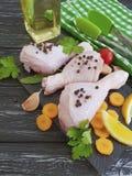 Τα ακατέργαστα πόδια πουλιών κοτόπουλου, λεμόνι, σκόρδο, μαϊντανός, καρότα γευμάτων, προετοιμάζουν το πετρέλαιο σε ένα μαύρο ξύλι Στοκ Εικόνα