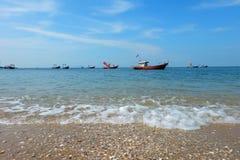 Τα αλιευτικά σκάφη βρίσκονται στην άγκυρα θαλασσίως, και τα ζωηρόχρωμων κοχύλια παραλιών και στοκ εικόνα