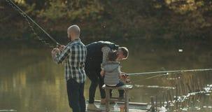 Τα αλιεύοντας άτομα κινηματογραφήσεων σε πρώτο πλάνο στη γέφυρα που πιάνει τα ψάρια, μπαμπάς ενθάρρυναν το γιο του στην αλιεία απόθεμα βίντεο
