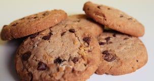 Τα αμερικανικά μπισκότα ύφους με την περιστροφή τσιπ σοκολάτας και σταφίδων σε ένα λευκό παρουσιάζουν σε ένα κίτρινο υπόβαθρο o P απόθεμα βίντεο