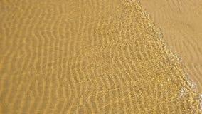 τα αμμώδη ακτών φωτεινά μικρά κύματα νερού αερακιού διαφανή σαφή διαμορφώνουν ένα σχέδιο στην άμμο στοκ εικόνες