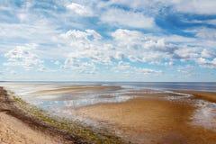 Τα αμμώδη τεντώματα ακτών στην απόσταση Στοκ Φωτογραφίες