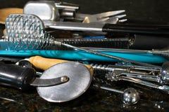 Τα ανάμεικτα εργαλεία κουζινών ώθησαν μαζί στο μετρητή στοκ εικόνες