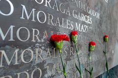 Τα αναμνηστικά λουλούδια βάζουν ενάντια στα ονόματα των θυμάτων Στοκ Εικόνα