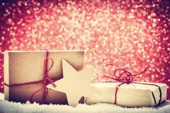 Τα αναδρομικά αγροτικά δώρα Χριστουγέννων, παρουσιάζουν στο χιόνι ακτινοβολούν επάνω backgr Στοκ Εικόνες