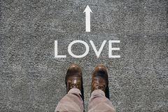 Τα ανθρώπινα παπούτσια βλέπουν άνωθεν, αγάπη λέξης και ένα βέλος που δείχνει τις κατευθύνσεις με το διάστημα αντιγράφων για το κε στοκ φωτογραφία με δικαίωμα ελεύθερης χρήσης