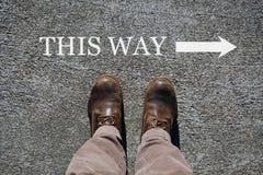 Τα ανθρώπινα παπούτσια βλέπουν άνωθεν, λέξεις αυτός ο τρόπος και ένα βέλος που δείχνει τις κατευθύνσεις με το διάστημα αντιγράφων στοκ εικόνα με δικαίωμα ελεύθερης χρήσης