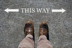 Τα ανθρώπινα παπούτσια βλέπουν άνωθεν, λέξεις αυτός ο τρόπος και ένα βέλος που δείχνει τις κατευθύνσεις με το διάστημα αντιγράφων στοκ φωτογραφία με δικαίωμα ελεύθερης χρήσης