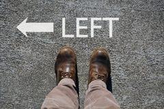 Τα ανθρώπινα παπούτσια βλέπουν άνωθεν, λέξη που αφήνονται και ένα βέλος που δείχνει τις κατευθύνσεις με το cpy διάστημα για το κε στοκ εικόνες με δικαίωμα ελεύθερης χρήσης