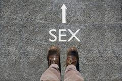 Τα ανθρώπινα παπούτσια βλέπουν άνωθεν, φύλο λέξης και ένα βέλος που δείχνει την κατεύθυνση με το διάστημα αντιγράφων στοκ φωτογραφία