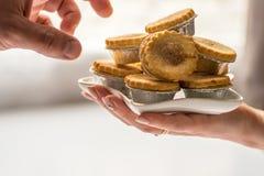 Τα ανθρώπινα χέρια άποψης κινηματογραφήσεων σε πρώτο πλάνο παίρνουν τα πικάντικα Χριστούγεννα κομματιάζουν τις πίτες από το πιάτο Στοκ φωτογραφία με δικαίωμα ελεύθερης χρήσης