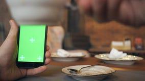 Τα ανθρώπινα χέρια είναι εκμετάλλευση Smartphone με την πράσινη οθόνη στον καφέ απόθεμα βίντεο