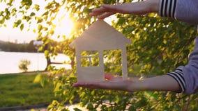 Τα ανθρώπινα χέρια κρατούν το σπίτι στο ηλιοβασίλεμα απόθεμα βίντεο