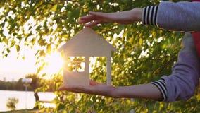 Τα ανθρώπινα χέρια κρατούν το σπίτι στο ηλιοβασίλεμα φιλμ μικρού μήκους