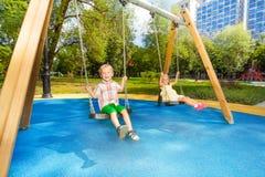 Ταλαντεμένος στο πάρκο, το αγόρι και το κορίτσι Στοκ Φωτογραφίες