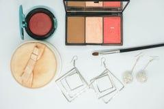 Τα απομονωμένα καλλυντικά, αποτελούν τη βούρτσα, τη διαφανή σκόνη και τα χαριτωμένα σκουλαρίκια Στοκ Φωτογραφίες