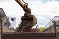 Τα απόβλητα κατασκευής φορτώνονται από το φτυάρι εκσκαφέων Στοκ Φωτογραφίες