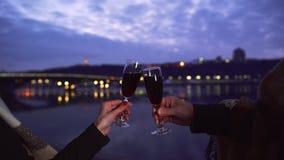 Τα αρσενικά και θηλυκά γυαλιά κρασιού λαβής χεριών κλείνουν επάνω Γυαλιά κρασιού γυαλιών κουδουνίσματος ζεύγους στο υπόβαθρο των  φιλμ μικρού μήκους