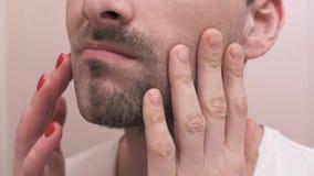 Τα αρσενικά και θηλυκά χέρια αγγίζουν το πρόσωπο μετά από να ξυρίσουν απόθεμα βίντεο