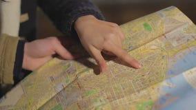 Τα αρσενικά και θηλυκά χέρια που κρατούν την πόλη χαρτογραφούν και που ψάχνουν την οδό, τουρισμός, κινηματογράφηση σε πρώτο πλάνο απόθεμα βίντεο