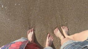 Τα αρσενικά και θηλυκά πόδια στέκονται στην αμμώδη παραλία απόθεμα βίντεο